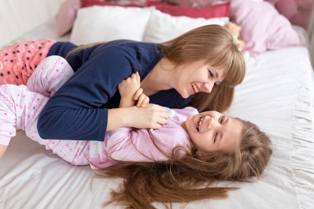 Mała dziewczynka spędza czas na zabawie z mamą leżąc w łóżku.