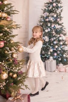 Mała dziewczynka spędza czas przy dekorowaniu choinki