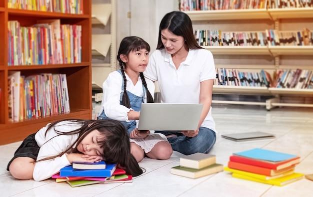 Mała dziewczynka śpi, jej starsza siostra uczy się korzystać z laptopa z piękną nauczycielką, wokół rozmywa się światło