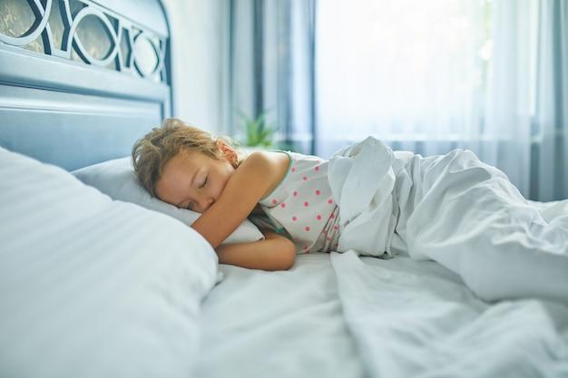 Mała dziewczynka śpi na dużym i wygodnym łóżku z białą pościelą po południu w domu