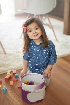 Mała dziewczynka sprząta po zabawie
