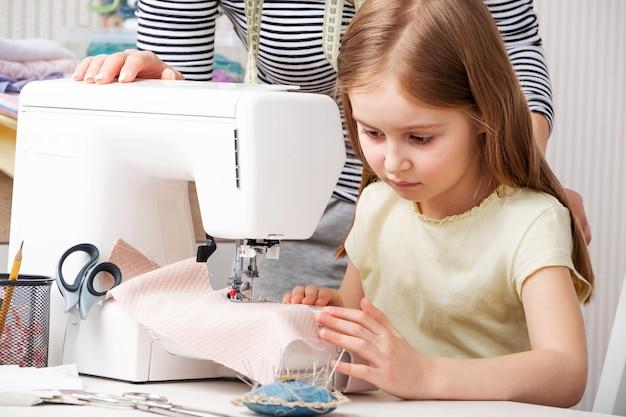 Mała dziewczynka starannie pracuje z maszyną do szycia