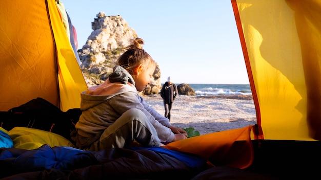 Mała dziewczynka stawia buty, siedząc w namiocie kempingowym na pięknej porannej plaży.