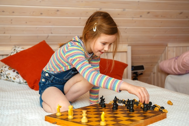 Mała dziewczynka stawia figury na szachownicy. gra w szachy