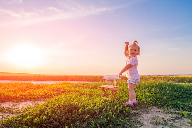 Mała dziewczynka steruje dronem za pomocą pilota w terenie