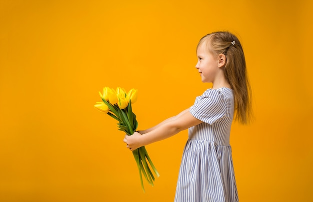 Mała dziewczynka stoi bokiem i trzyma w rękach bukiet tulipanów