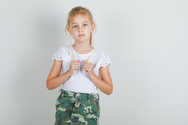 Mała dziewczynka stoi i niesie plecak w białej koszulce
