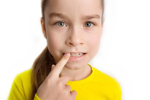 Mała dziewczynka stoi na białym tle z pięknym uśmiechem, dziećmi krzywymi zębami, stomatologią dziecięcą. zbliżenie krzywe zęby. konieczna jest korekcja wad zgryzu. zdjęcie wysokiej jakości