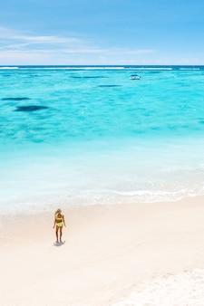 Mała dziewczynka stoi na plaży le morne na oceanie indyjskim na wyspie mauritius.