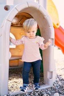 Mała dziewczynka stoi na progu domku z zabawkami na placu zabaw