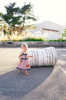 Mała dziewczynka stoi obok białych opon na parkingu