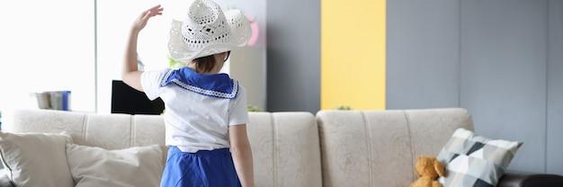 Mała dziewczynka stoi plecami z żółtą walizką