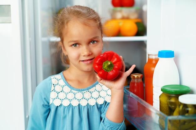 Mała dziewczynka stoi przed lodówką i wybiera jedzenie