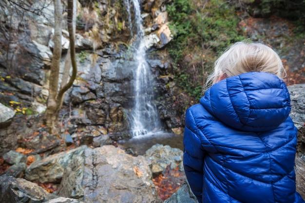 Mała dziewczynka stoi przed wodospadem.