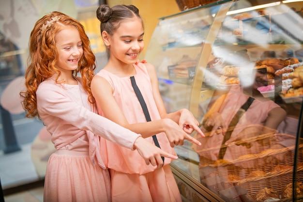 Mała dziewczynka stoi przy oknie w kawiarni i wybiera bułki i ciasta, a małe koleżanki stoją przy witrynie w kawiarni i wybierają bułeczki i ciasta.