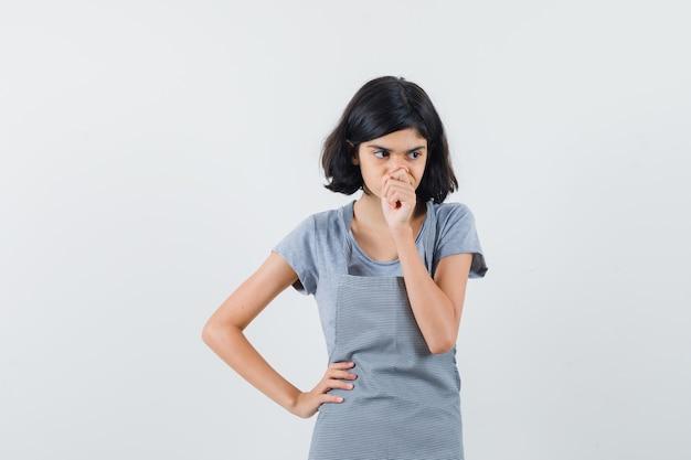 Mała dziewczynka stoi w myślącej pozie w t-shirt, fartuch i niepewny patrząc. przedni widok.