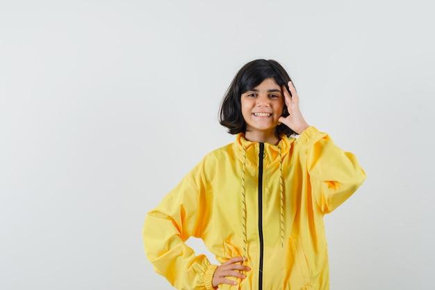 Mała dziewczynka stoi w myślącej pozie w żółtej bluzie z kapturem i patrzy wesoło, widok z przodu.