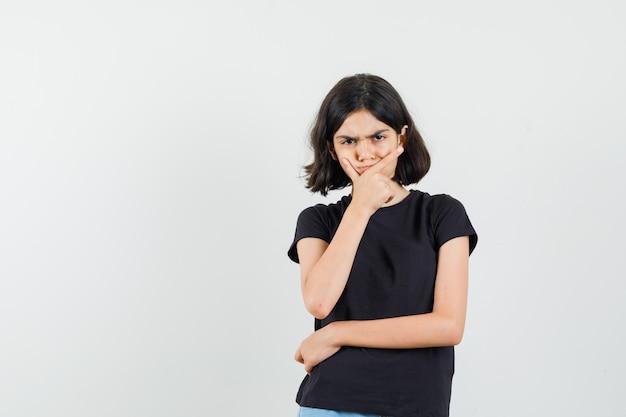 Mała dziewczynka stoi w myśleniu poza w czarnej koszulce i patrząc poważnie. przedni widok.