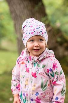 Mała dziewczynka stoi w parku