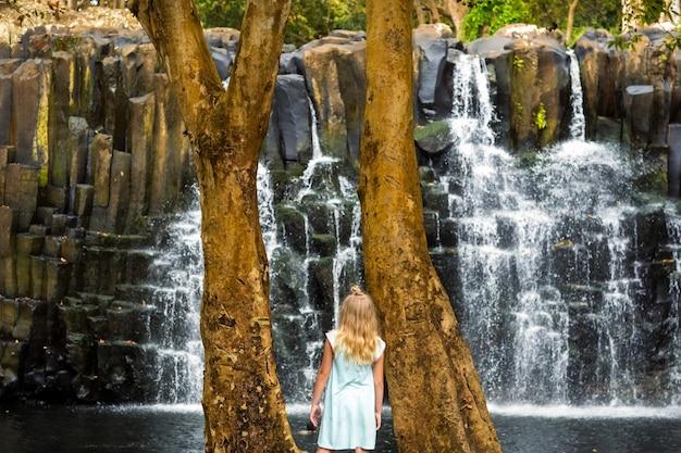 Mała dziewczynka stoi w pobliżu wodospadu rochester na wyspie mauritius. wodospad w dżungli tropikalnej wyspy mauritius