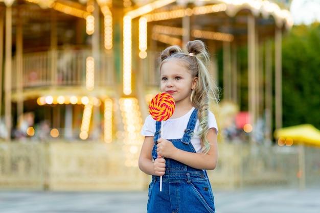 Mała dziewczynka stoi w wesołym miasteczku z dużym lollipopem