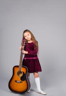Mała dziewczynka stoi z gitarą akustyczną