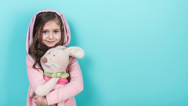 Mała dziewczynka stoi z zabawkarskim królikiem
