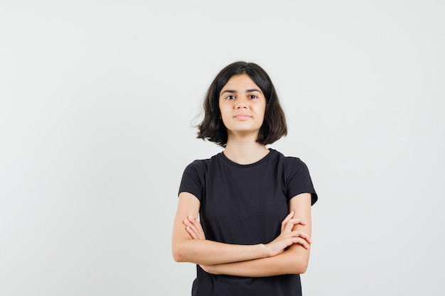 Mała dziewczynka stoi ze skrzyżowanymi rękami w czarnej koszulce i wygląda pewnie. przedni widok.