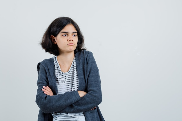 Mała dziewczynka stoi ze skrzyżowanymi rękami w koszulce, kurtce i wygląda smutno
