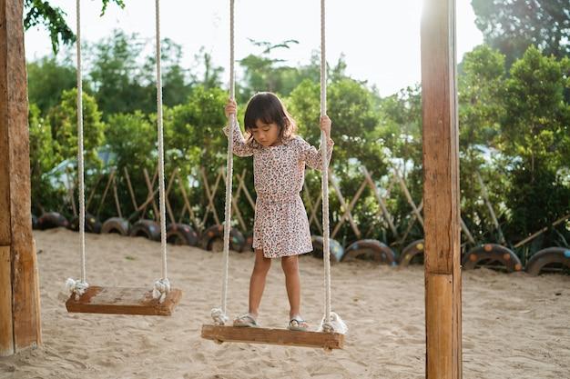 Mała dziewczynka stojąca na drewnianej huśtawce sama