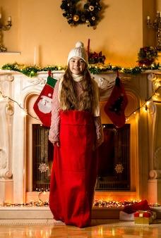 Mała dziewczynka stojąca w czerwonej torbie świętego mikołaja w salonie przy kominku