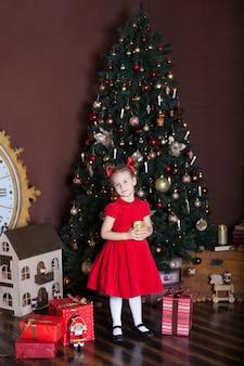 Mała dziewczynka stojąca w pobliżu choinki i prezent