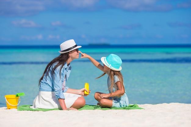 Mała dziewczynka stosuje słońce śmietankę jej macierzysty nos