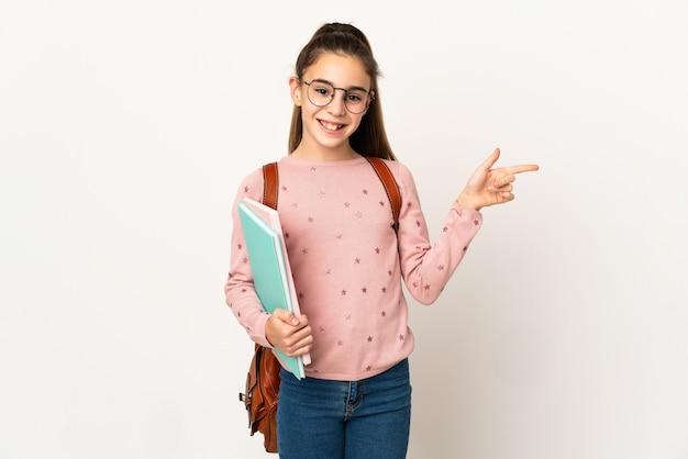 Mała dziewczynka student na izolowanej ścianie palcem wskazującym w bok