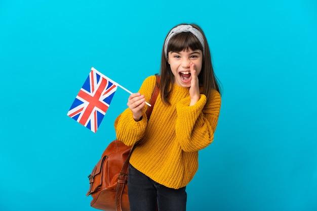 Mała dziewczynka studiująca angielski na białym tle na niebieskim tle krzycząca z szeroko otwartymi ustami