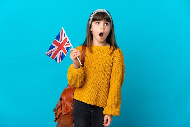 Mała dziewczynka studiująca angielski na białym tle na niebieskim tle patrząca w górę i ze zdziwionym wyrazem twarzy