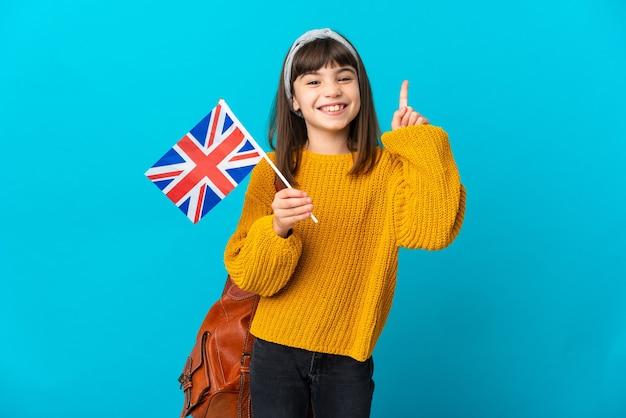 Mała dziewczynka studiuje angielski na białym tle na niebieskiej ścianie, pokazując i podnosząc palec na znak najlepszych