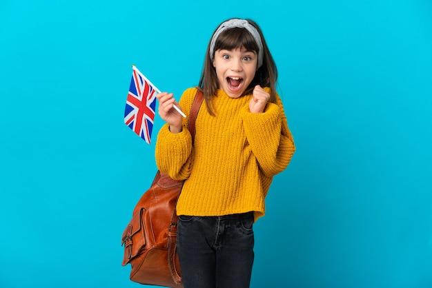 Mała dziewczynka studiuje angielski na białym tle na niebieskiej ścianie świętuje zwycięstwo w pozycji zwycięzcy