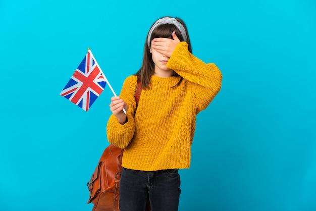 Mała dziewczynka studiuje angielski na białym tle na niebieskim tle obejmujące oczy rękami. nie chcę czegoś widzieć