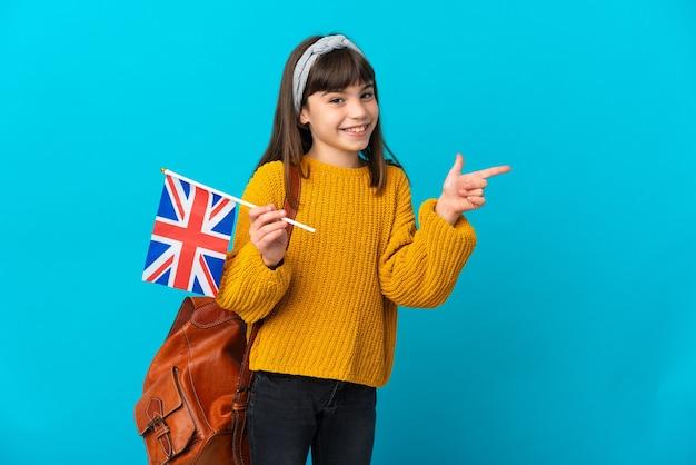 Mała dziewczynka studiuje język angielski na białym tle na niebieskim tle, wskazując palcem w bok