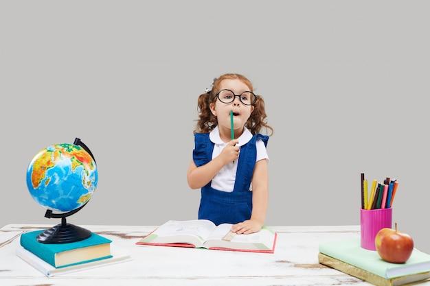 Mała dziewczynka studiuje podczas gdy będący ubranym skalowanie nakrętkę na szarej odosobnionej ścianie