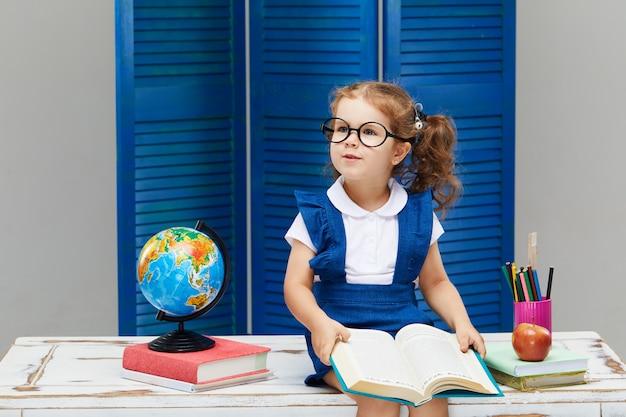 Mała dziewczynka studiuje podczas noszenia czapki ukończenia szkoły