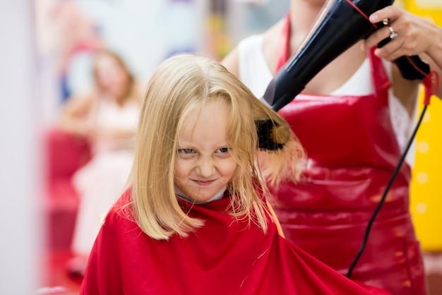 Mała dziewczynka suche włosy w sklepie fryzjerskim.