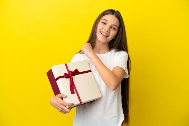 Mała dziewczynka świętująca zwycięstwo trzymająca prezent na odosobnionym żółtym tle