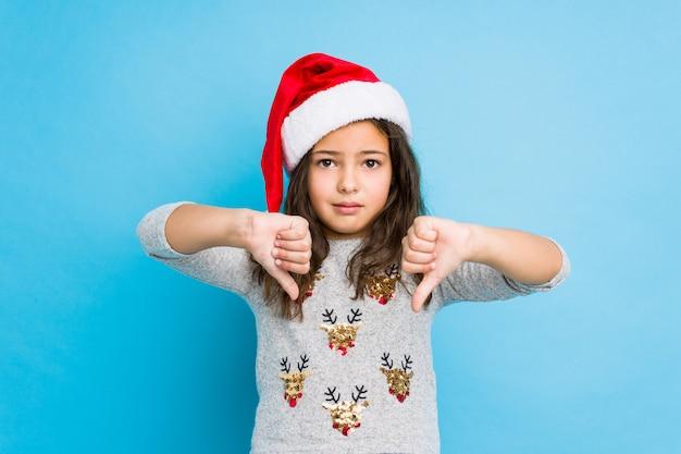 Mała dziewczynka świętuje boże narodzenie dzień pokazuje kciuka puszek i wyraża niechęć.