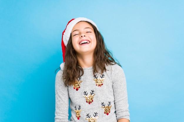 Mała dziewczynka świętuje boże narodzenie zrelaksowany i szczęśliwy śmiejąc się, szyja rozciągnięta pokazując zęby.