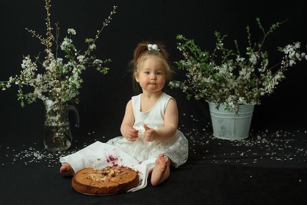 Mała dziewczynka świętuje swoje pierwsze urodziny. dziewczyna je swój pierwszy tort.