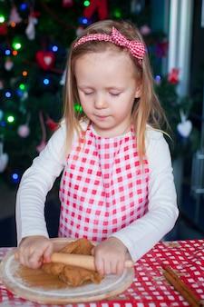 Mała dziewczynka szczęśliwy z wałkiem do pieczenia pierniki na boże narodzenie