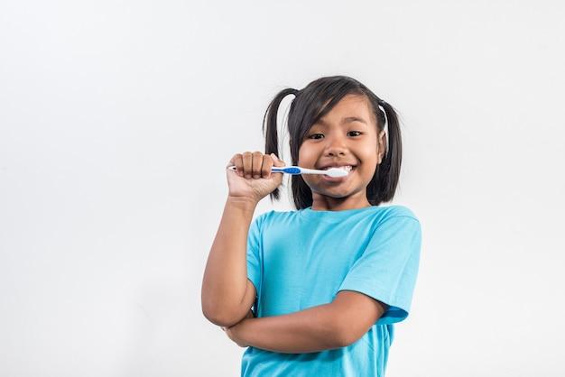 Mała dziewczynka szczotkowanie zębów w studio strzał