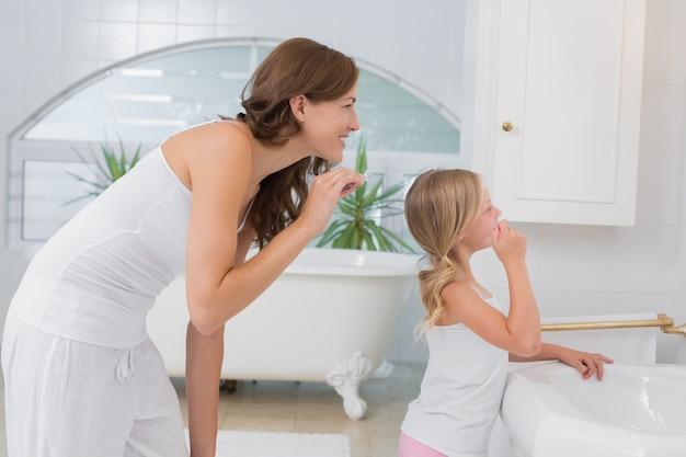 Mała dziewczynka szczotkuje zęby z matką